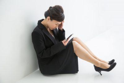 スマホ片手に悩む女性のイメージ